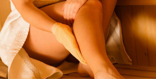 woman using exfoliating glove on leg